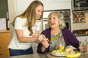 1Heart Caregiver helping senior with meal.
