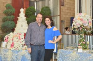 Susan and James Irvine at 2018 standing in front of the replica of their wedding cake and guest table exhibit at the 2018 Orange County Fair in Costa Mesa, California
